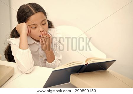 Boring Literature. Girl Child Reads Book While Sit Table White Background. Schoolgirl Studying And R