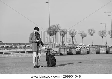 poster of Traveler with suitcase waiting transportation to airport railway station. Ready to travel. Carry travel bag. Business trip. Man bearded hipster travel with big luggage bag on wheels. Let travel begin.