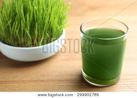 Glass Of Spirulina Drink And Wheatgrass On Wooden Table, Closeup With Space For Text