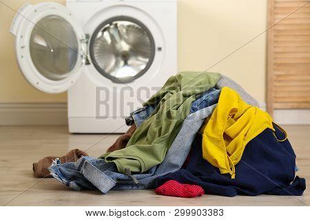 Pile Of Dirty Laundry Near Washing Machine Indoors