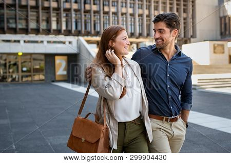 Mature couple enjoying city walk together outdoors. Happy smiling young couple walking while embracing on street. Laughing man and woman looking to each others while walking out from movie theater.