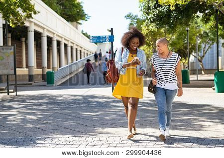 Two young women walking while using mobile phone on urban city street. Cheerful woman doing online shopping with friend outdoor. African american girl showing smartphone screen to friend.