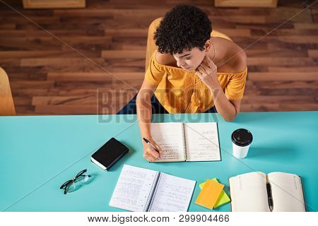 High angle view of african girl studying in library. Young brazilian student copying notes from book at cafeteria. Top view of concentrated college student in class taking notes during the lesson.