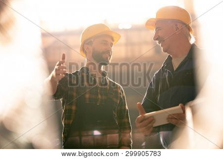 Young and senior colleagues in workwear and hardhats discussing new industrial or machinebuilding equipment
