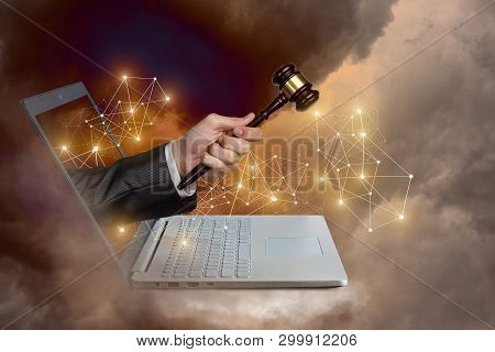 The Concept Of Bankruptcy In The Network. Hand With Hammer Coming Out Of A Laptop Against The Sky.