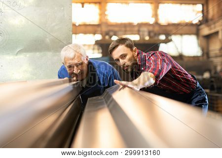 Mature foreman and his subordinate in workwear looking at new metallic workpieces or details for industrial machines poster