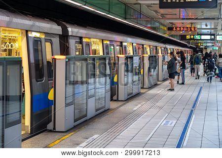 Taipei, Taiwan - April 15, 2019 : Taipei Metro Station Hall And Platform. Subway Passengers Walk Thr