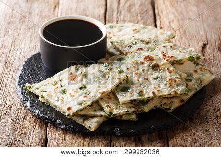 Simple Recipe For Chinese Fried Onion Pancakes Served With Sauce Close-up On A Board. Horizontal