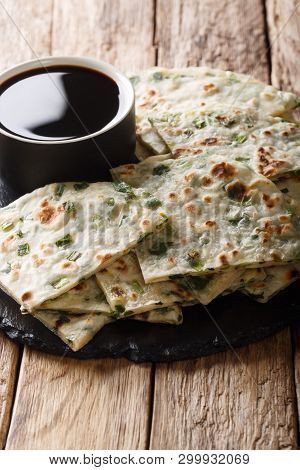 Flatbread Fried Onion Pancakes Served With Sauce Close-up On A Board. Vertical