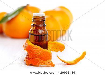 bottle of aromatic essence and fresh orange on white isolated background