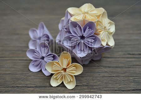 Purple And Yellow Origami Kusudama Flower On Wooden Background