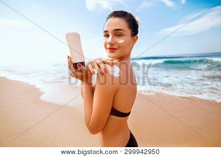 Woman Apply Sun Cream On Tanned  Back. Skin And Body Care. Sun Protection. Portrait Of Female In Bik