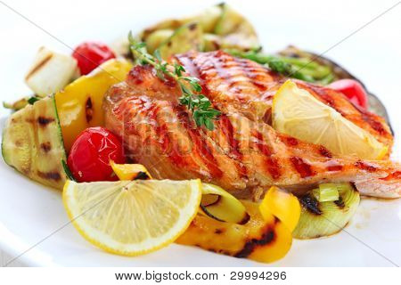 delicious grilled salmon steak with grilled vegetables on white plate