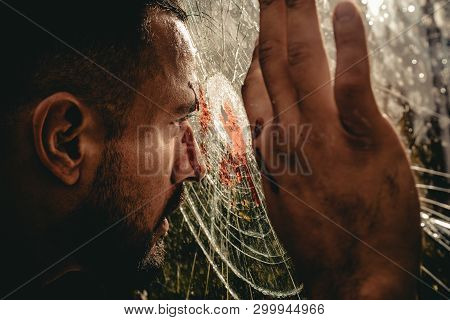 Victim Of War. Wounded Man Victim Looking Through Broken Glass. Crime Or Violence Victim. Victim Of