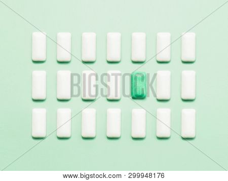 One Green Chewing Gum  Standing Out Of White Chewing Gums. Concept Of Individuality, Uniqueness Or L