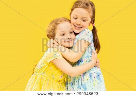 Beautiful Emotional Little Girls Isolated On Yellow Background. Half-lenght Portrait Of Two Happy Si