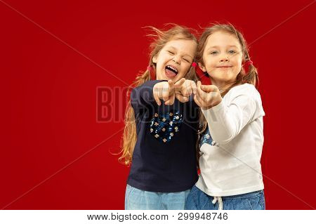 Beautiful Emotional Little Girls Isolated On Red Studio Background. Half-lenght Portrait Of Happy Si