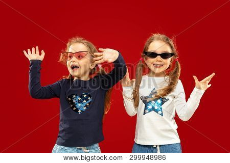 Beautiful Emotional Little Girl Isolated On Red Background. Half-lenght Portrait Of Happy Sisters Or
