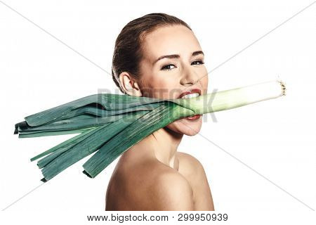 Young woman with raw leek in mouth on white background. Diet concept.