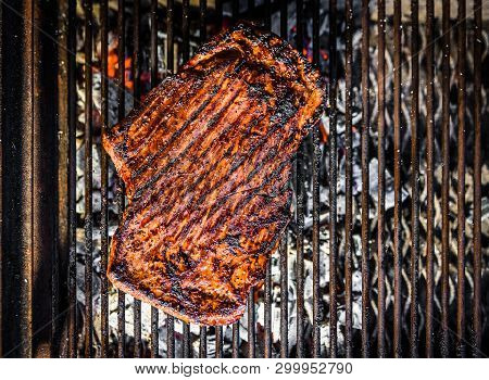 Grilling Marinated Beef Flank Steak On Hot Coals Barbecue Grill.