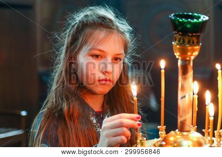 Little Girl Puts A Candle In Church. Orthodoxy And Children