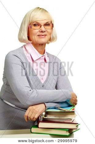 Pretty elderly lady leaning over a pile of books isolated on white background