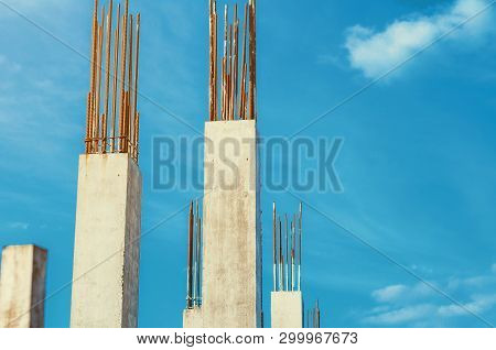 Concrete walls and pillars with metal fixtures at a construction site on a blue sky background. poster