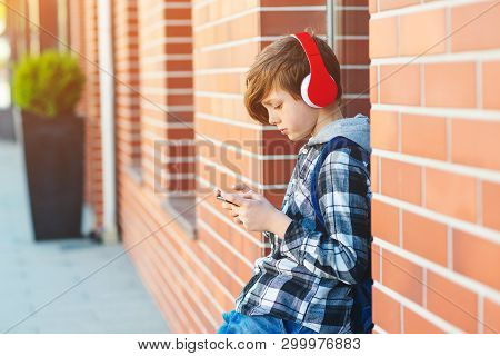 Stylish Kid Boy With Headphones Using Phone At City Street. Young Boy Plays Online Game At Smartphon