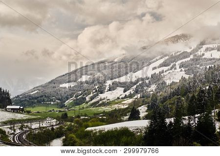 View On Grassy Meadows With Melting Snow And Snowy Mountains In Gastein Valley In Spring One Cloudy