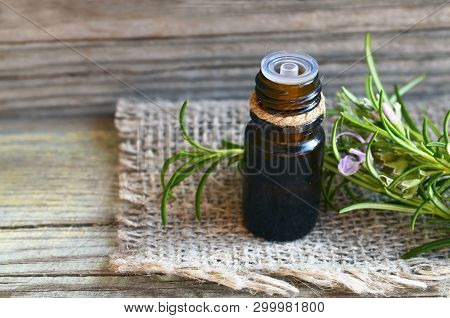 Rosemary Essential Oil In A Glass Dropper Bottle With Fresh Green Rosemary Herb On Old Wooden Table