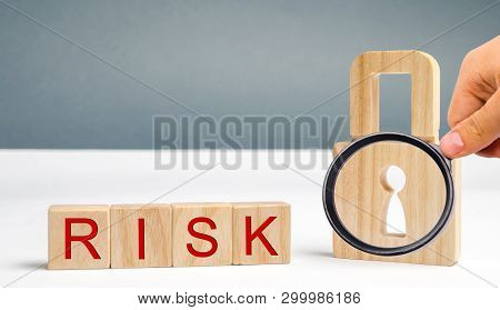 Wooden Blocks With The Word Risk And Lock. Imperfect Security System. High Risk Of Hacking And Theft