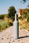 one gray bottle on the road from the tiles, the village, rural alcoholism, drunkenness. alcoholic illness. wine natural drink. wine poster