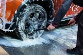 Cleaning with soap suds at self-service car wash. Man washes black wheel of his orange car with brush. Soapy water runs down. poster