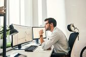 Busy working. Handsome bearded trader in formal wear and eyeglasses is analyzing trading charts and financial data on computer screens while sitting in his modern office. poster