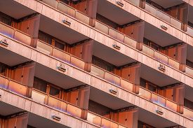 Architectural Pattern, Red Facade With Balconies In The Light Of The Setting Sun. Old Hotel In Budap