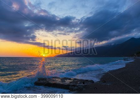 Beautiful Shoreline Scene With Waves At Sunset Beams