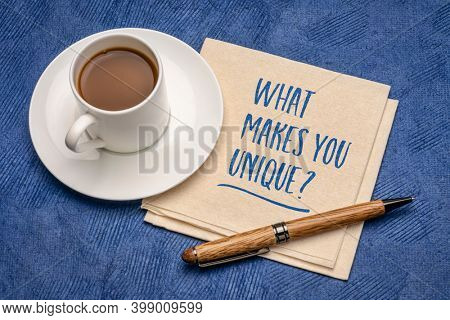 What makes you unique? Handwriting on a napkin with a cup of coffee. Personal branding and development concept.