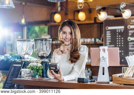 Asian Small Business Young Owner Holding Contactless Nfs Technology Machine To Checking And Billing