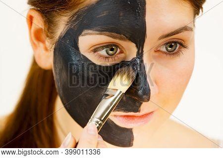 Female Applying Black Mud Facial Mask