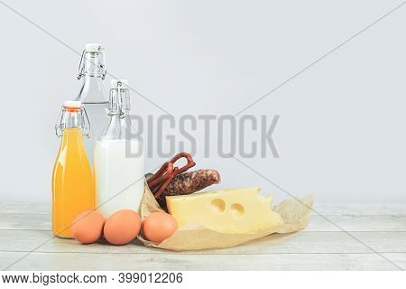 Plain Paper Bag With Dairy Produce, Eggs Cheese With Water Milk Glass Bottles On Grey. Food Delivery
