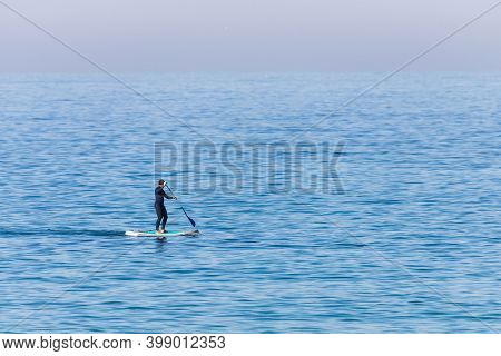 Stand Up Paddle Boarder In Wetsuit Paddling On A Sea. Minimalist Image.