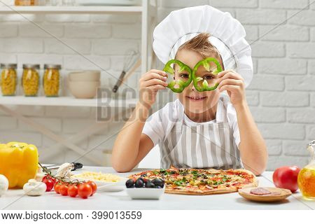 Little Boy In Chef Hat And An Apron Cooking Pizza In The Kitchen. The Child Holding Green Bell Peppe