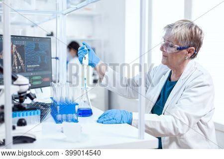 Senior Scientist Taking Solution From Glass Flask Using Molecular Pipette. People In Innovative Phar