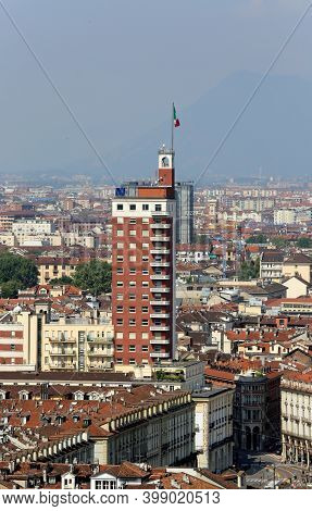 Turin, To, Italy - August 27, 2015: Very Tall Skyscraper With The Italian Flag And The Houses Below