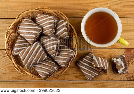 Wicker Basket With Gingerbread, Broken Striped Gingerbread, Yellow Glass Cup With Tea On Wooden Tabl