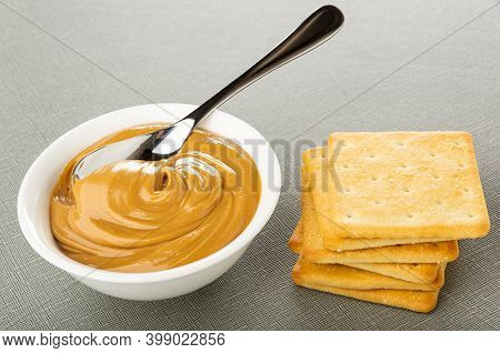 White Glass Bowl With Peanut Butter, Crackers On Gray Table