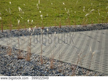 Flower Bed By The Parking Lot Mulched With Pebbles. It Is Light Non-flammable And Is Not Carried Awa