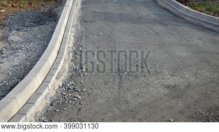 Installation Of Concrete Curb Into Concrete. In The Space Of The Road, Which So Far Has Only A Concr