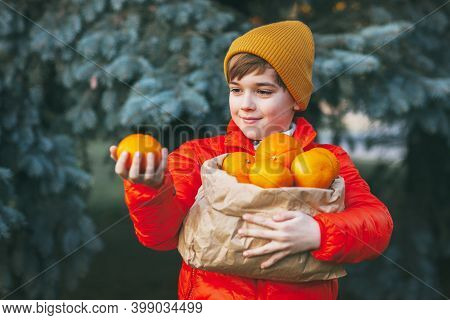 A Boy In A Bright Orange Jacket And Yellow Hat Holds A Large Bag Of Oranges In His Hands Against The