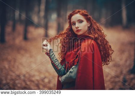 A beautiful red-haired girl of the Middle Ages walks through the forest. Celtic culture. Fantasy world.